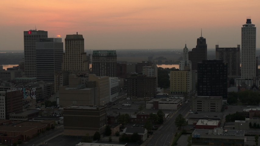 5.7K stock footage aerial video circling office towers with view of setting sun, Downtown Memphis, Tennessee Aerial Stock Footage | DX0002_186_033