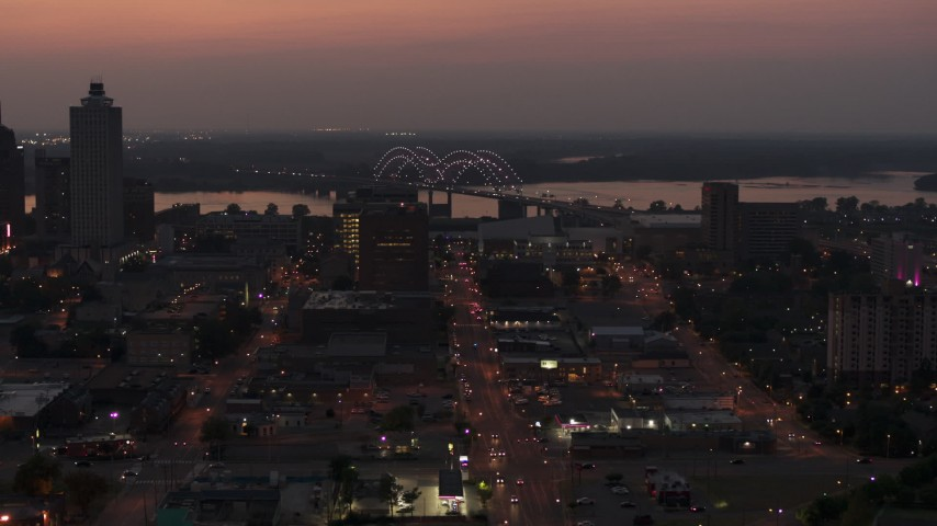 5.7K stock footage aerial video fly away from and past Hernando de Soto Bridge, seen from Downtown Memphis, Tennessee at twilight Aerial Stock Footage | DX0002_187_009