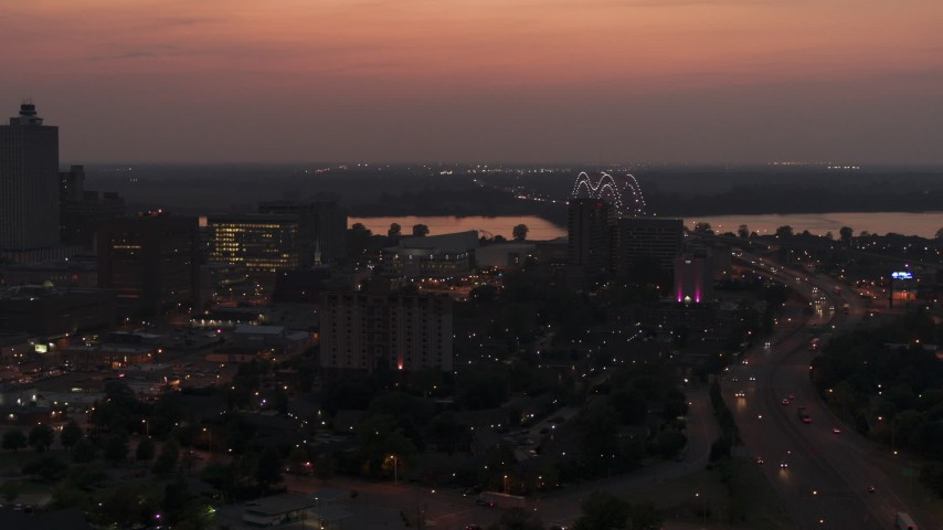 5.7K stock footage aerial video of the Hernando de Soto Bridge, seen from Downtown Memphis, Tennessee at twilight Aerial Stock Footage | DX0002_187_010