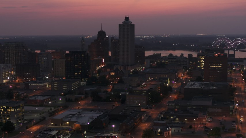 5.7K stock footage aerial video of the 100 North Main office tower near the bridge at twilight, Downtown Memphis, Tennessee Aerial Stock Footage | DX0002_187_018