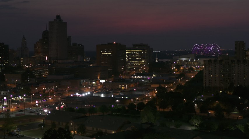 5.7K stock footage aerial video of city buildings between office tower and bridge at night, Downtown Memphis, Tennessee, seen during descent Aerial Stock Footage | DX0002_187_028