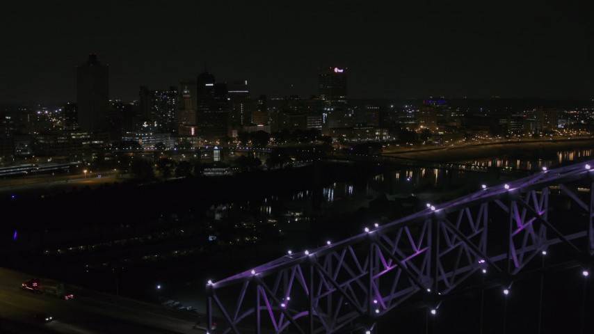 5.7K stock footage aerial video of the downtown skyline, reveal the bridge with purple lights at night, Downtown Memphis, Tennessee Aerial Stock Footage | DX0002_187_035