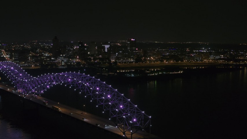 5.7K stock footage aerial video ascend past the bridge with purple lights for a view of the skyline at night, Downtown Memphis, Tennessee Aerial Stock Footage | DX0002_187_037