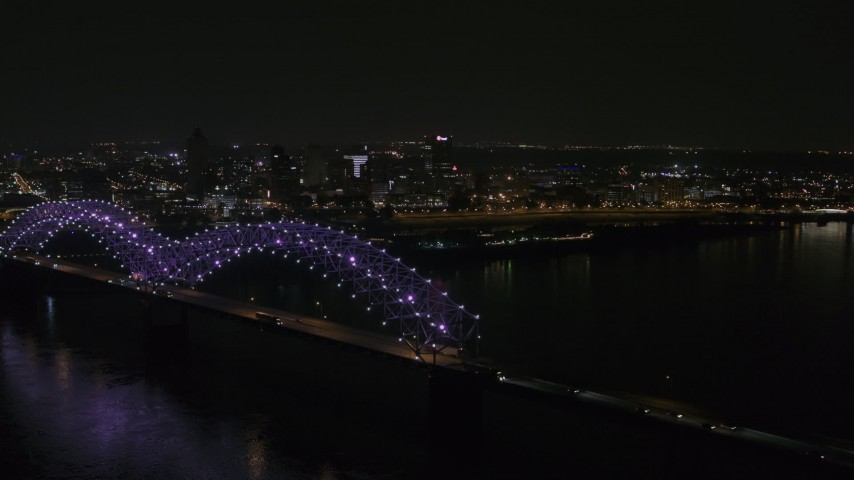 5.7K stock footage aerial video flying by the bridge with colorful lights with a view of the skyline at night, Downtown Memphis, Tennessee Aerial Stock Footage | DX0002_187_038