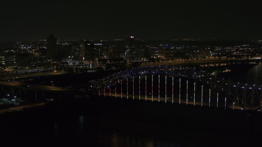 5.7K stock footage aerial video of the skyline seen while passing the bridge with colorful lights at night, Downtown Memphis, Tennessee Aerial Stock Footage | DX0002_187_040