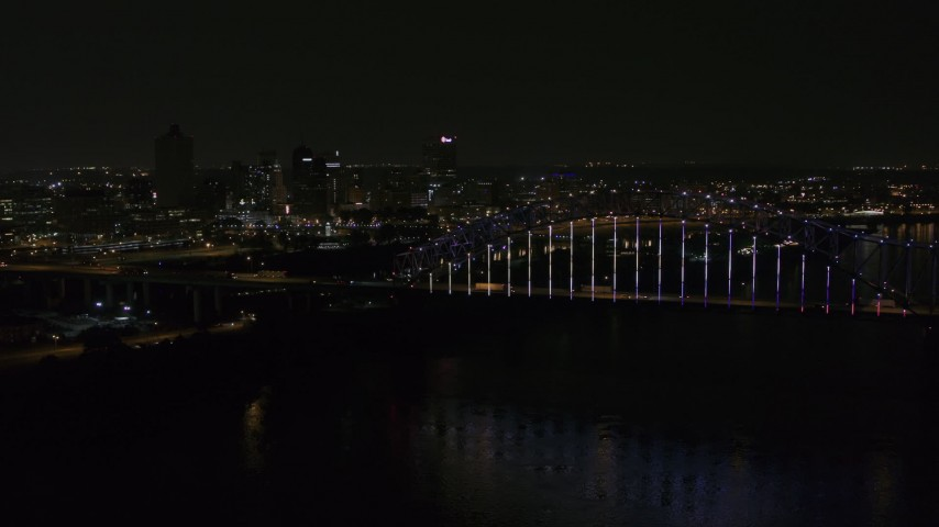 5.7K stock footage aerial video of flying away from the skyline and bridge with colorful lights at night, Downtown Memphis, Tennessee Aerial Stock Footage | DX0002_187_041