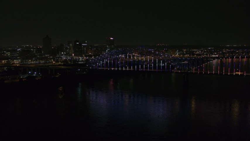 5.7K stock footage aerial video of the skyline behind bridge with colorful lights at night, Downtown Memphis, Tennessee Aerial Stock Footage | DX0002_187_042
