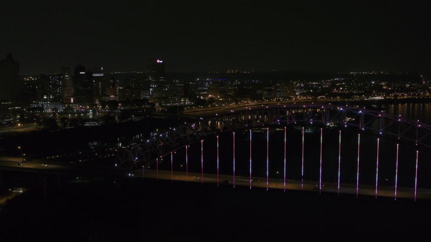 5.7K stock footage aerial video fly over the bridge with colorful lights toward skyline at night, Downtown Memphis, Tennessee Aerial Stock Footage | DX0002_187_048