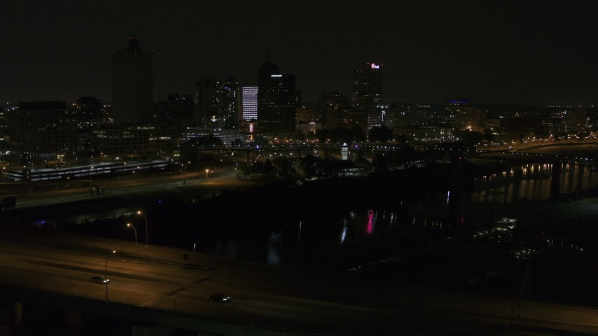 5.7K stock footage aerial video view of the skyline while descending near the bridge at night, Downtown Memphis, Tennessee Aerial Stock Footage | DX0002_187_054