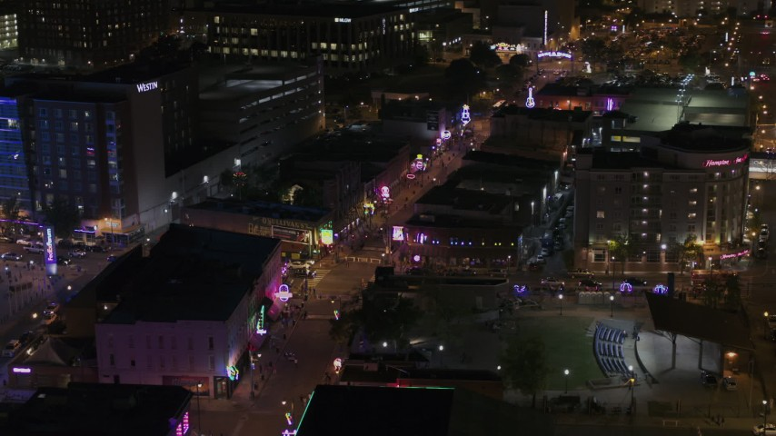 5.7K stock footage aerial video orbit Beale Street intersection with bright lights and signs at nighttime, Downtown Memphis, Tennessee Aerial Stock Footage | DX0002_188_008