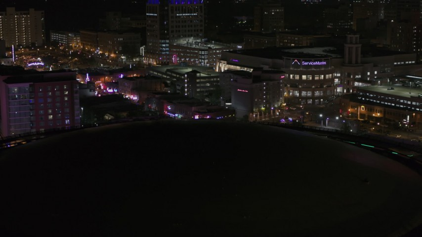 5.7K stock footage aerial video of Beale Street at nighttime while descending by arena, Downtown Memphis, Tennessee Aerial Stock Footage | DX0002_188_012