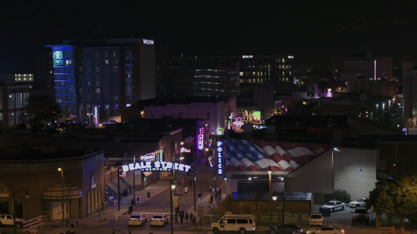 5.7K stock footage aerial video of passing the Beale Street sign for view of clubs and restaurants at nighttime, Downtown Memphis, Tennessee Aerial Stock Footage | DX0002_188_040