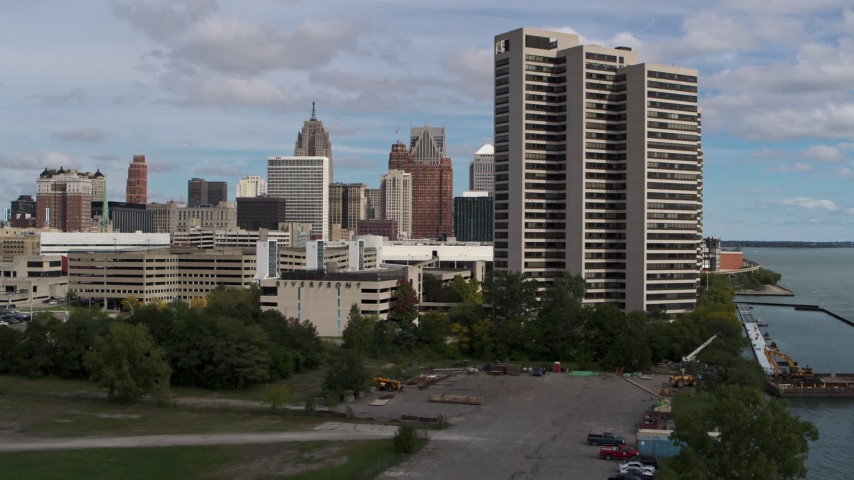 5.7K stock footage aerial video descend by apartment complex with view of skyline in Downtown Detroit, Michigan Aerial Stock Footage | DX0002_189_024