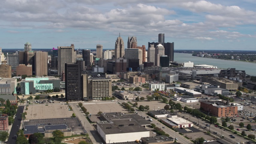 5.7K stock footage aerial video the skyline behind office buildings, Downtown Detroit, Michigan Aerial Stock Footage | DX0002_189_026