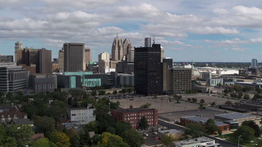 5.7K stock footage aerial video descend and pass office buildings, skyline in background, Downtown Detroit, Michigan Aerial Stock Footage | DX0002_189_031