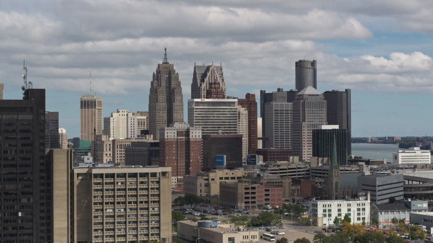 5.7K stock footage aerial video ascend near office buildings to focus on the skyline, Downtown Detroit, Michigan Aerial Stock Footage | DX0002_189_036