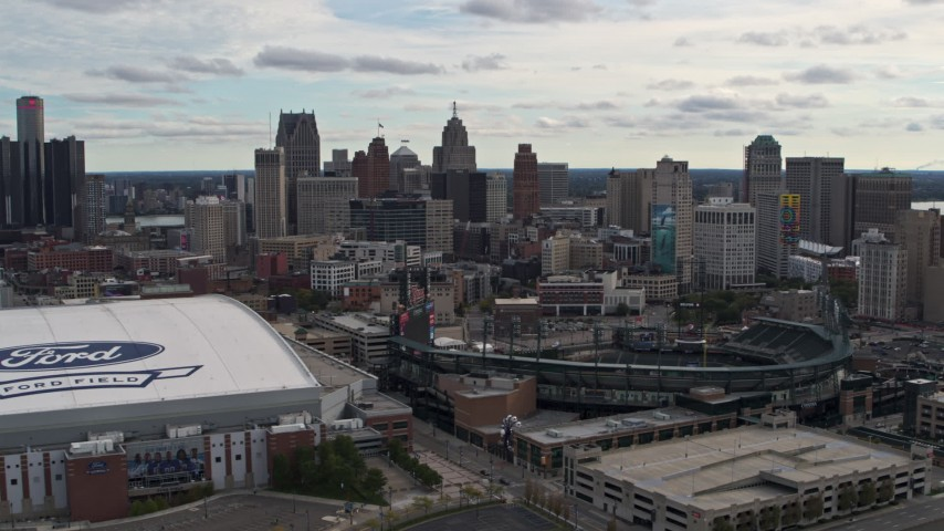 5.7K stock footage aerial video flying by baseball and football stadiums with view of skyline, Downtown Detroit, Michigan Aerial Stock Footage | DX0002_191_007