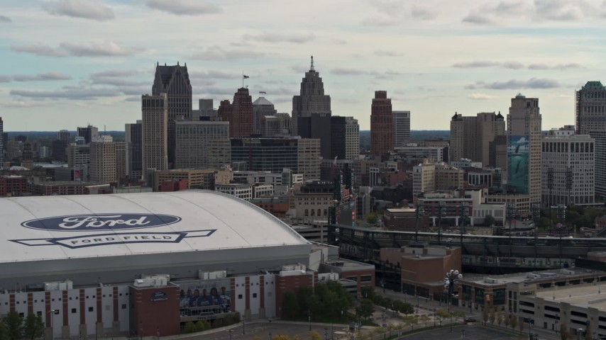 5.7K stock footage aerial video of the downtown skyline while passing by baseball and football stadiums, Downtown Detroit, Michigan Aerial Stock Footage | DX0002_191_022