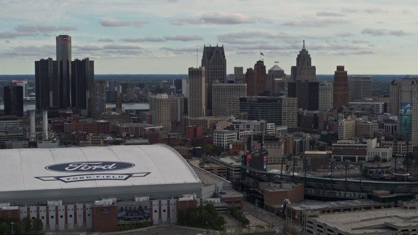 5.7K stock footage aerial video focus on the downtown skyline while flying by Comerica Park and Ford Field, Downtown Detroit, Michigan Aerial Stock Footage | DX0002_191_025