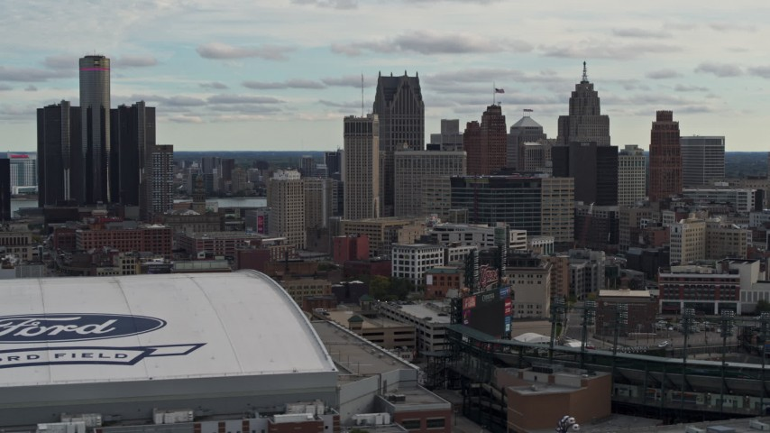 5.7K stock footage aerial video focus on downtown skyline while passing Ford Field and Comerica Park, Downtown Detroit, Michigan Aerial Stock Footage | DX0002_191_026