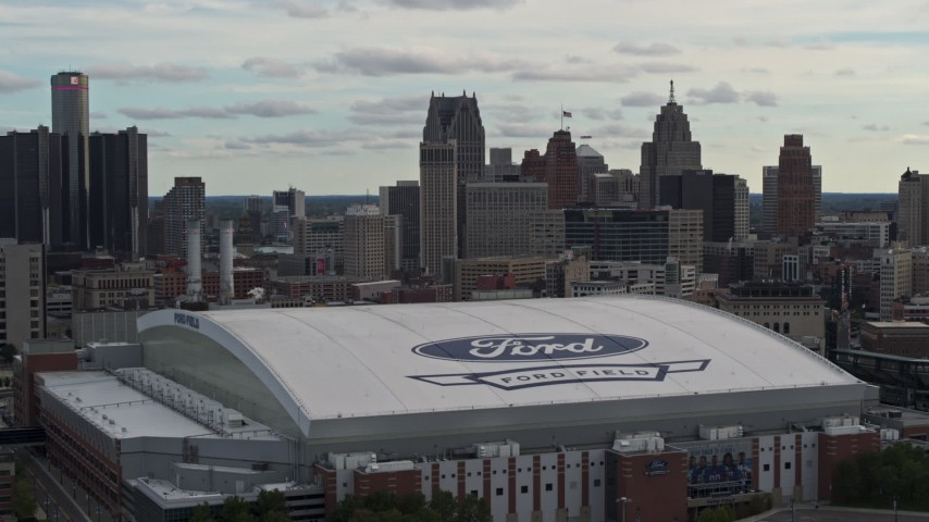 5.7K stock footage aerial video focus on downtown skyline and descend by Ford Field, Downtown Detroit, Michigan Aerial Stock Footage | DX0002_191_028