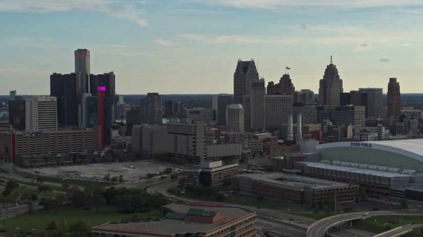 5.7K stock footage aerial video fly away from the skyline at sunset in Downtown Detroit, Michigan, reveal Ford Field Aerial Stock Footage | DX0002_191_037
