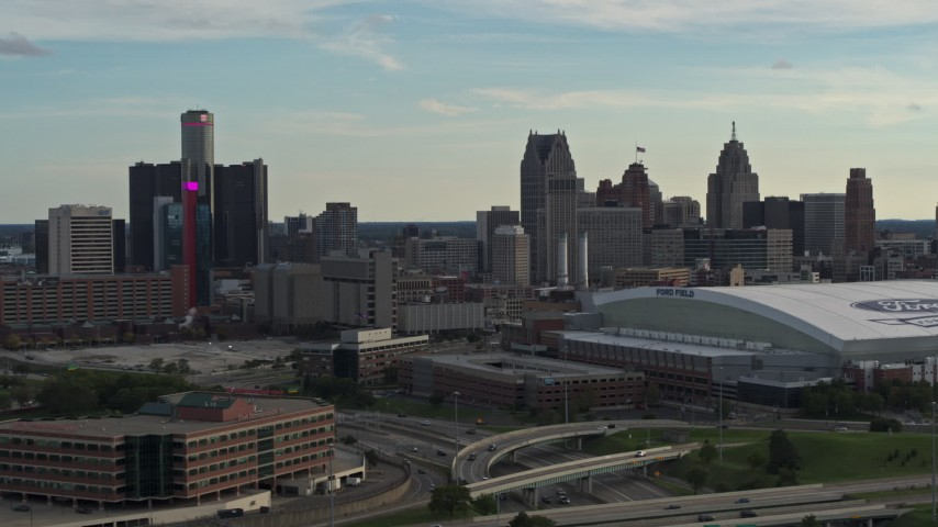 5.7K stock footage aerial video passing the football stadium, focus on the city skyline at sunset in Downtown Detroit, Michigan Aerial Stock Footage | DX0002_191_039