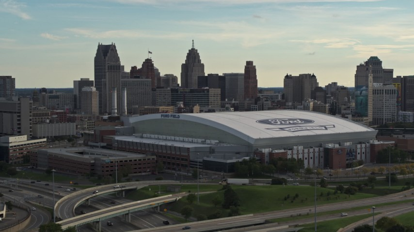 5.7K stock footage aerial video of a reverse view of the football stadium and the city skyline at sunset in Downtown Detroit, Michigan Aerial Stock Footage | DX0002_191_041