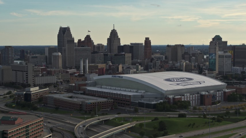 5.7K stock footage aerial video of slowly flying by the football stadium and the city skyline at sunset in Downtown Detroit, Michigan Aerial Stock Footage | DX0002_191_042
