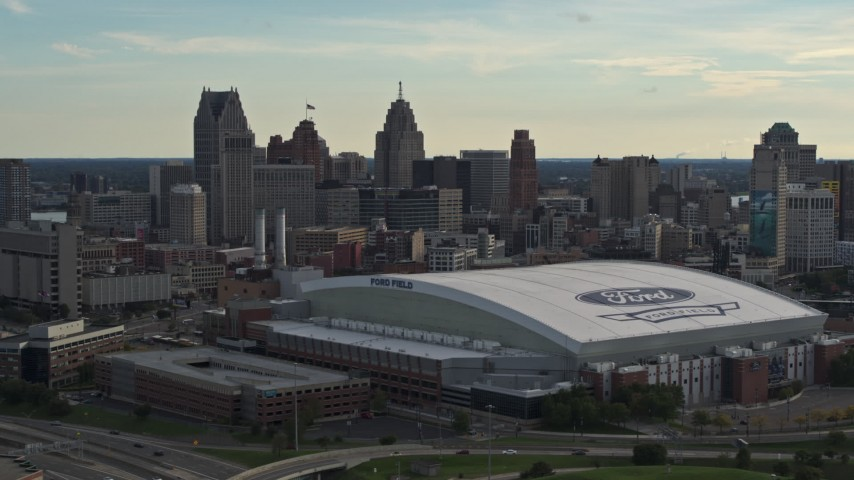 5.7K stock footage aerial video of slowly passing the football stadium and the city skyline at sunset in Downtown Detroit, Michigan Aerial Stock Footage | DX0002_191_043