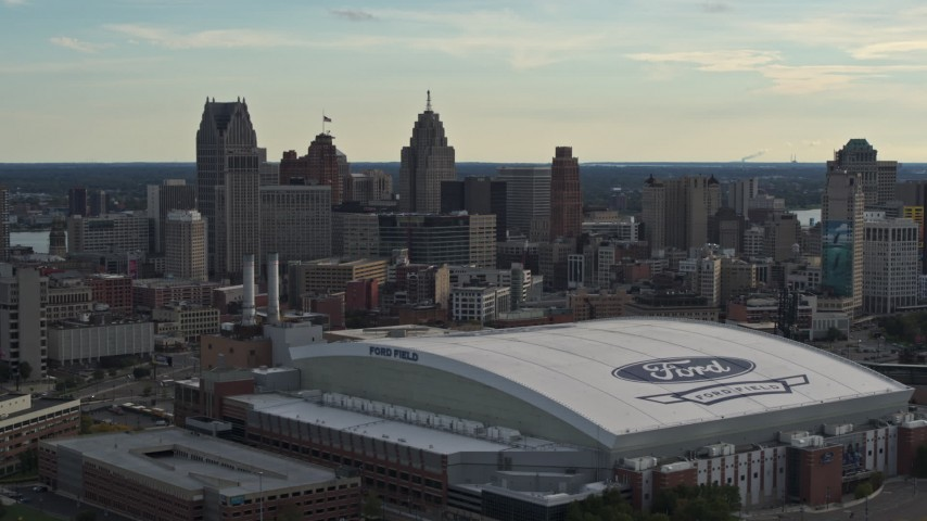 5.7K stock footage aerial video flyby Ford Field football stadium and the city skyline at sunset in Downtown Detroit, Michigan Aerial Stock Footage | DX0002_191_045