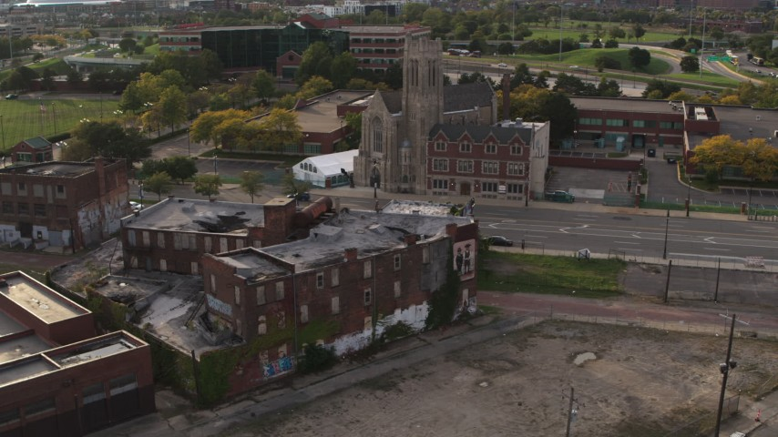 5.7K stock footage aerial video orbit an abandoned building and reveal a church at sunset, Detroit, Michigan Aerial Stock Footage | DX0002_192_014