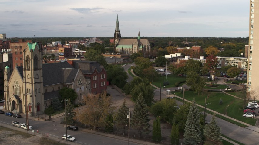 5.7K stock footage aerial video of a reverse view of a church from a second church at sunset, Detroit, Michigan Aerial Stock Footage | DX0002_192_020