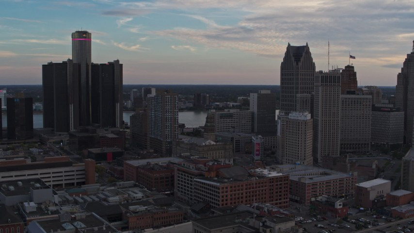 5.7K stock footage aerial video of flying by skyscrapers at sunset to reveal a hotel, Downtown Detroit, Michigan Aerial Stock Footage | DX0002_192_036