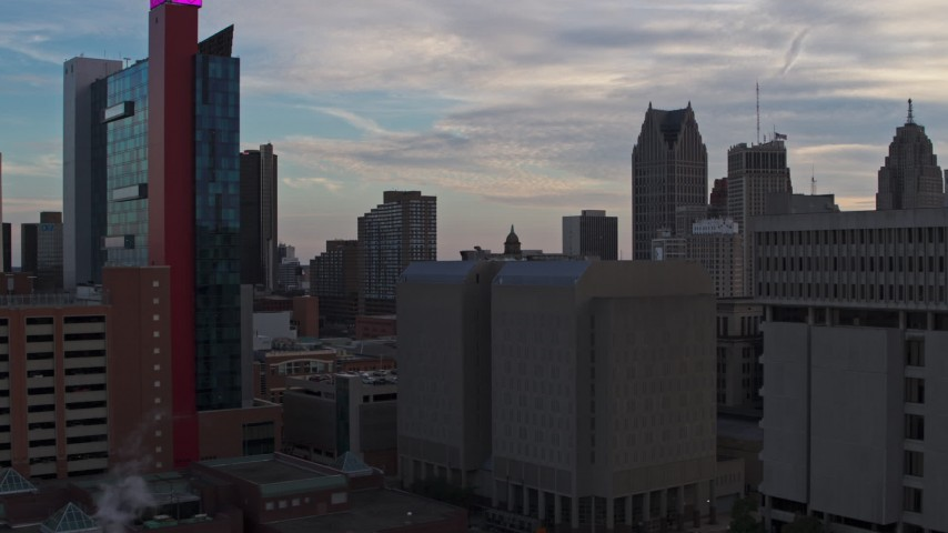 5.7K stock footage aerial video descend past skyscrapers at sunset to reveal a hotel, Downtown Detroit, Michigan Aerial Stock Footage | DX0002_192_038