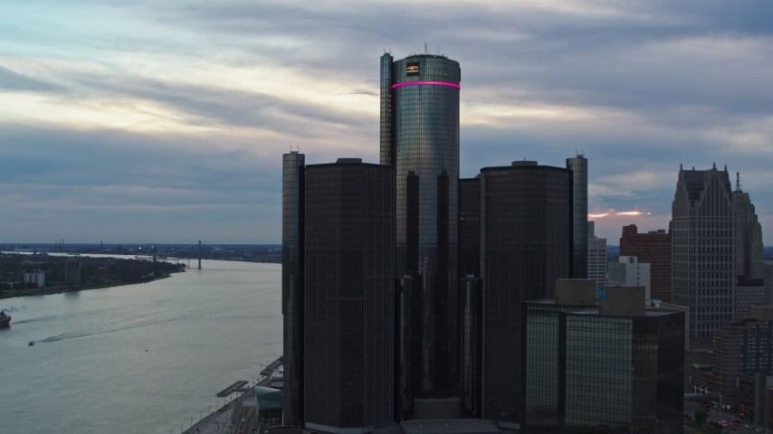 5.7K stock footage aerial video orbit and fly away from riverfront skyscraper at sunset, Downtown Detroit, Michigan Aerial Stock Footage | DX0002_192_040