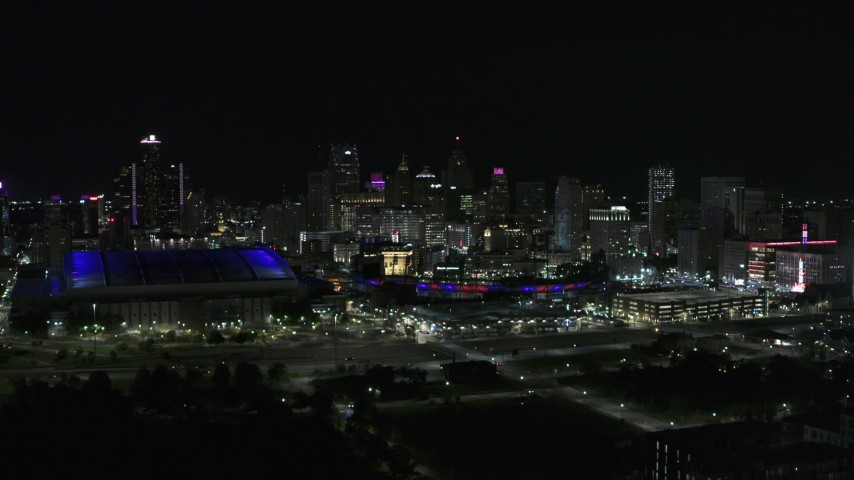 5.7K stock footage aerial video the skyline behind Ford Field and Comerica Park stadiums at night, Downtown Detroit, Michigan Aerial Stock Footage | DX0002_193_047