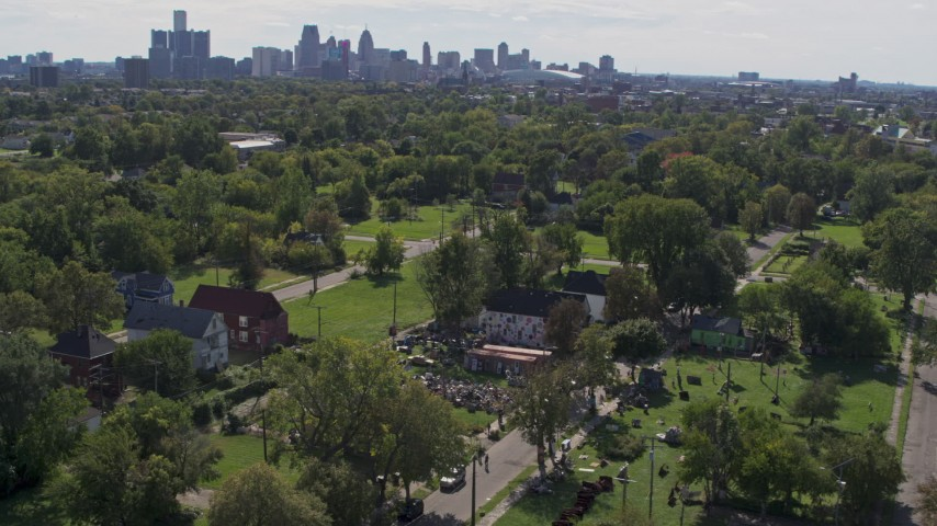 5.7K stock footage aerial video of circling the Heidelberg Project outdoor art display and urban homes, reveal the skyline in Detroit, Michigan Aerial Stock Footage | DX0002_195_009
