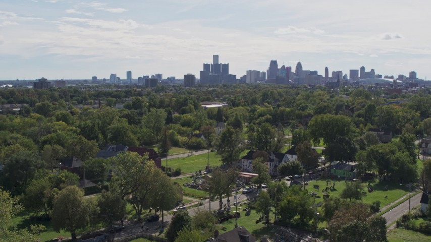 5.7K stock footage aerial video of the distant skyline seen from the Heidelberg Project outdoor art display and urban homes, Detroit, Michigan Aerial Stock Footage | DX0002_195_010