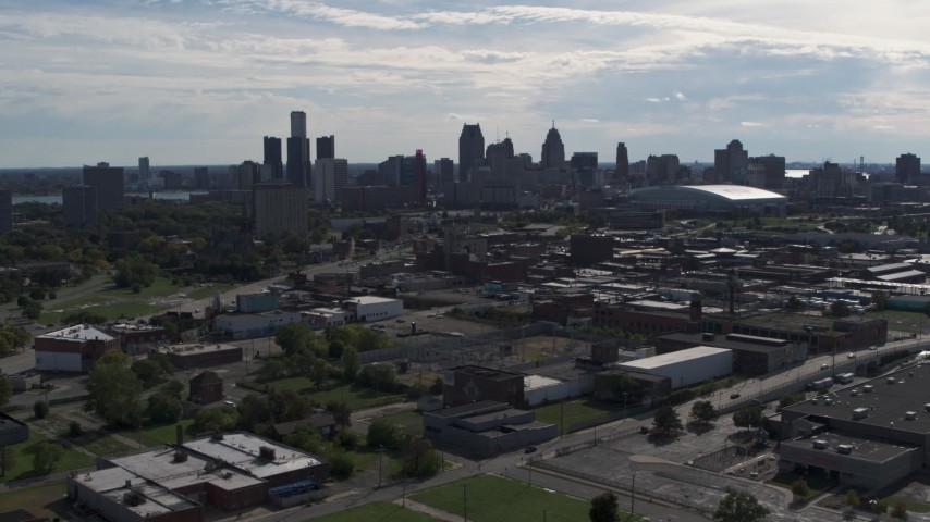 5.7K stock footage aerial video of flying by the city's skyline, seen from brick industrial buildings, Downtown Detroit, Michigan Aerial Stock Footage | DX0002_195_021