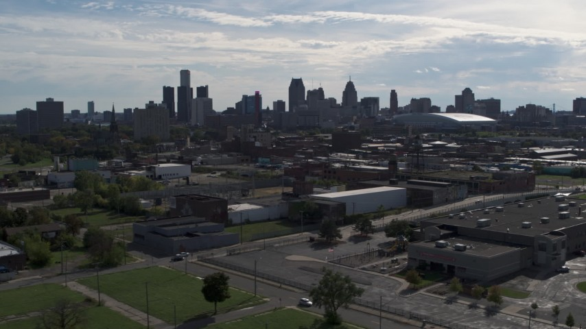 5.7K stock footage aerial video of passing by the city's skyline, seen from brick industrial buildings, Downtown Detroit, Michigan Aerial Stock Footage | DX0002_195_022