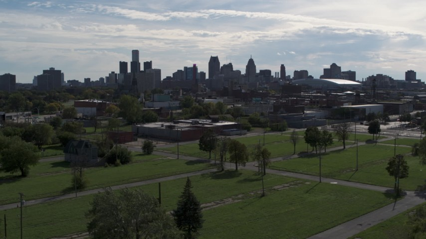 5.7K stock footage aerial video focus on the city's skyline while descending toward green lots, Downtown Detroit, Michigan Aerial Stock Footage | DX0002_195_023