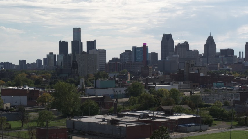 5.7K stock footage aerial video focus on the city's skyline while descending near brick buildings, Downtown Detroit, Michigan Aerial Stock Footage | DX0002_195_024