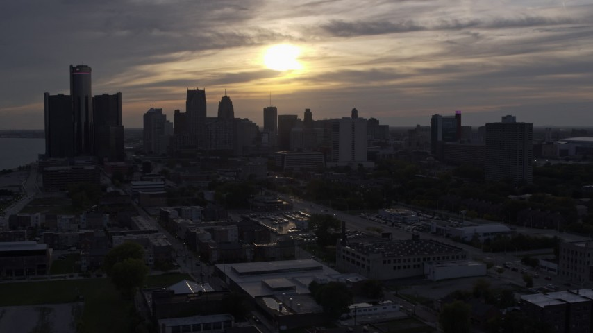 5.7K stock footage aerial video of the setting sun behind clouds above the Downtown Detroit skyline, Michigan Aerial Stock Footage | DX0002_197_001