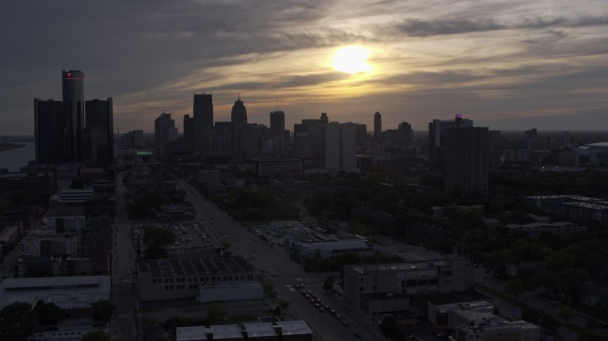 5.7K stock footage aerial video of flying by the setting sun behind clouds above the Downtown Detroit skyline, Michigan Aerial Stock Footage | DX0002_197_002