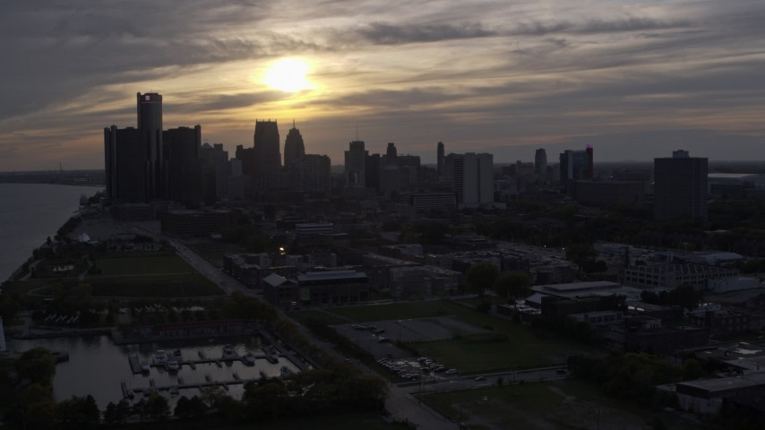 5.7K stock footage aerial video of passing by the setting sun behind clouds above the Downtown Detroit skyline, Michigan Aerial Stock Footage | DX0002_197_003