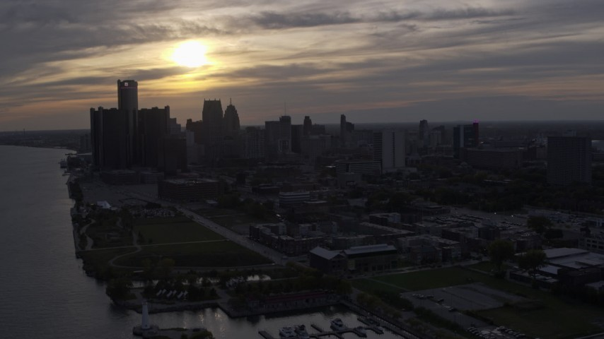 5.7K stock footage aerial video ascend and flyby the setting sun behind clouds above the Downtown Detroit skyline, Michigan Aerial Stock Footage | DX0002_197_004