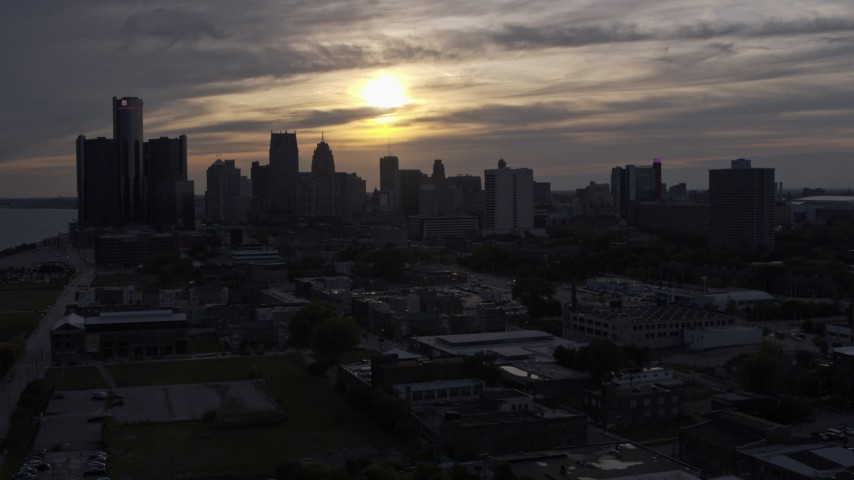 5.7K stock footage aerial video of flying by the city's skyline with the setting sun in the clouds above, Downtown Detroit, Michigan Aerial Stock Footage | DX0002_197_006