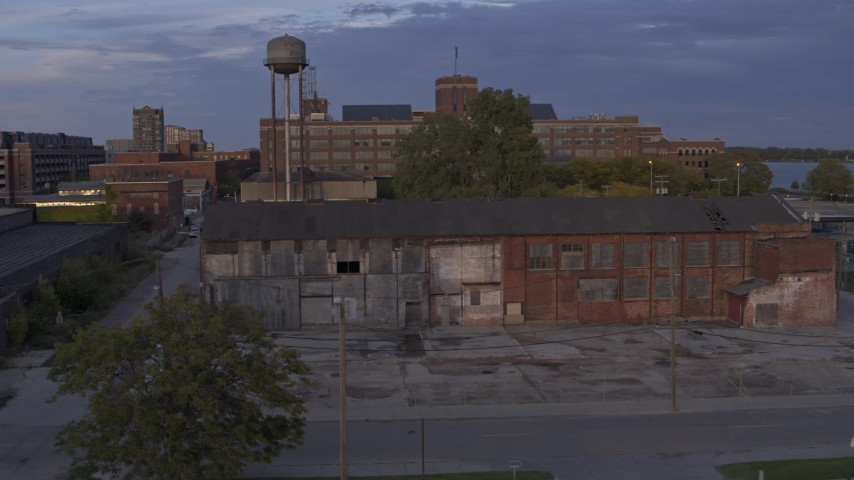 5.7K stock footage aerial video ascend by abandoned factory building and water tower at sunset, Detroit, Michigan Aerial Stock Footage | DX0002_197_015