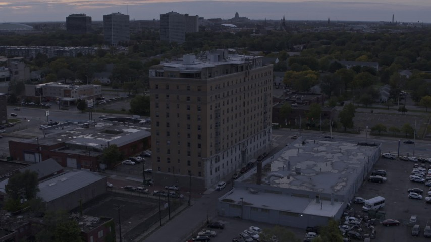 5.7K stock footage aerial video of flying away from an apartment building at sunset, Detroit, Michigan Aerial Stock Footage | DX0002_197_023